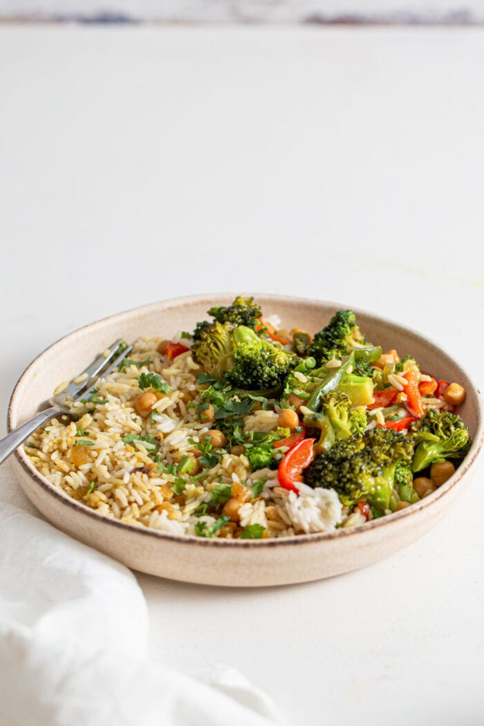 Bowl of rice, vegetables and chickpeas in a curry sauce. Fork rests in bowl.