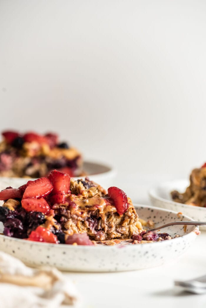 Front view of a plate of baked oatmeal topped with berries and peanut butter, fork rests on plate.