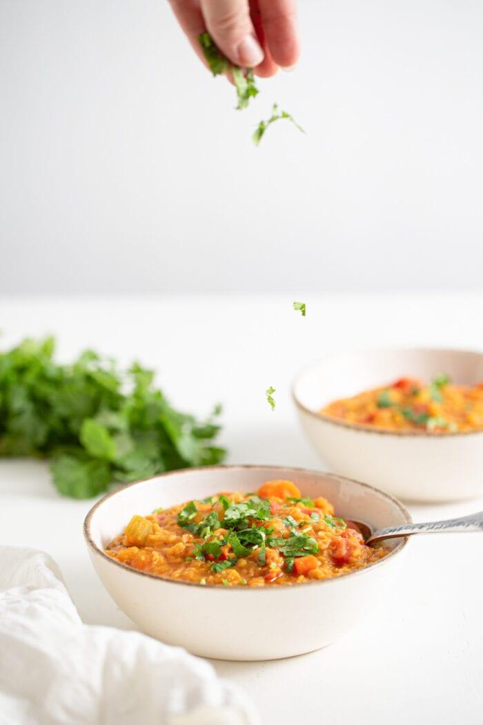 Hand spinkling cilantro over a bowl of lentil soup.
