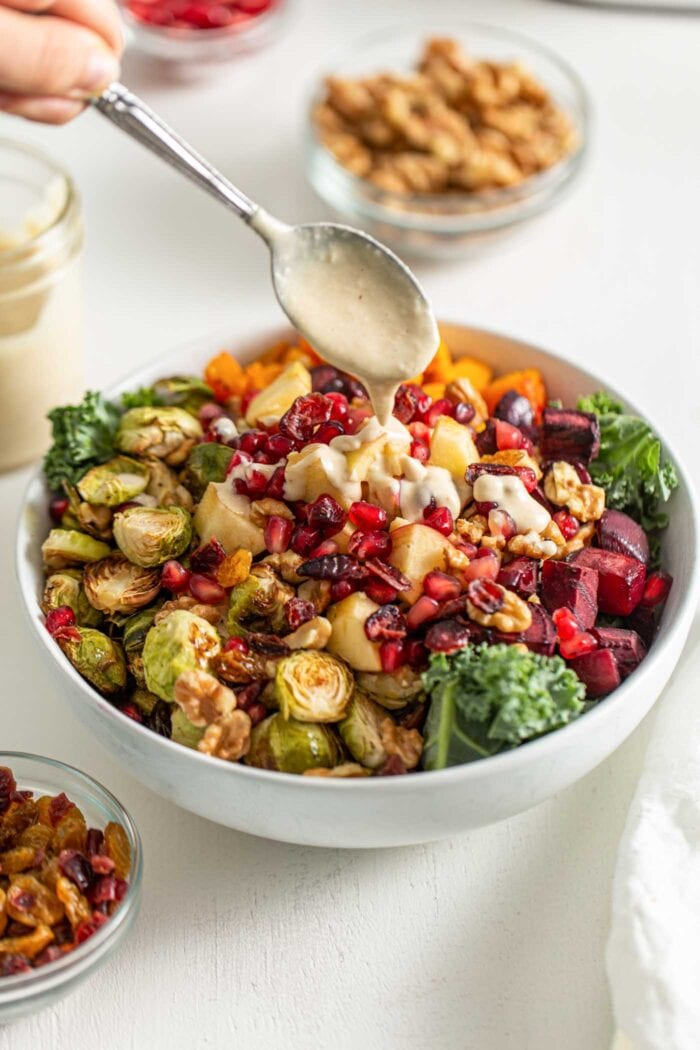 Drizzling a spoon of sauce over a salad with roasted vegetables and kale.