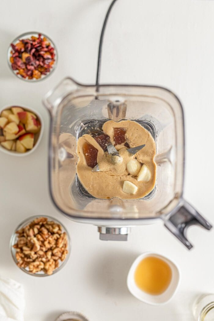Tahini, garlic and maple syrup in a blender container.