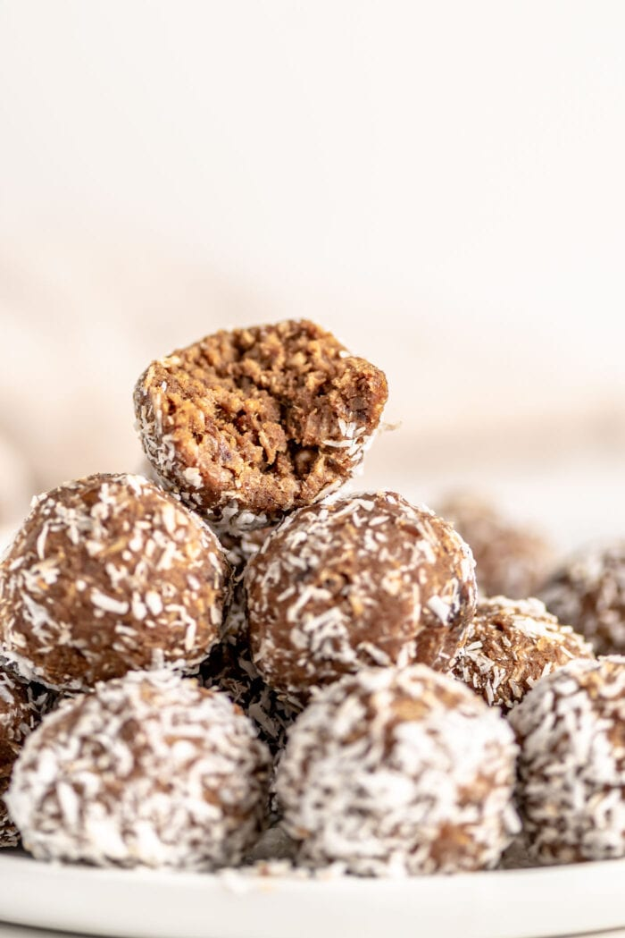 Stack of energy balls on a plate, one on top has bite taken out of it.