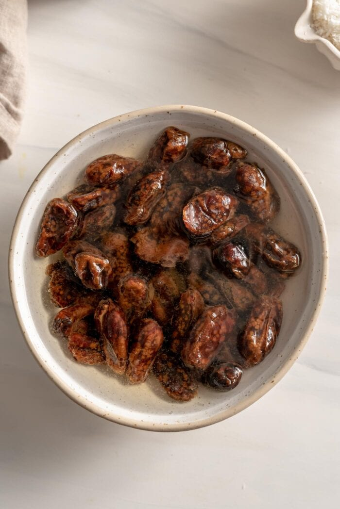 Dates soaking in water in a bowl.