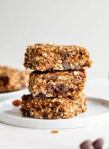 Close up front view of a stack of 3 oatmeal raisin chocolate chip bars on a small plate.