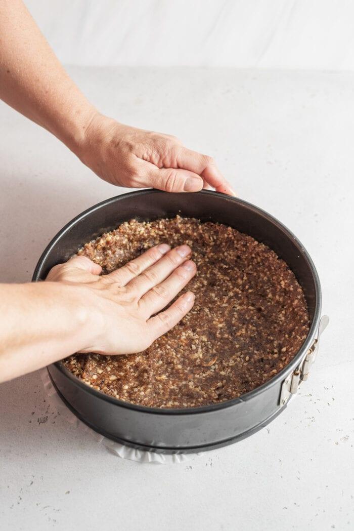 Hands pressing dough for a crust into a springform baking pan.