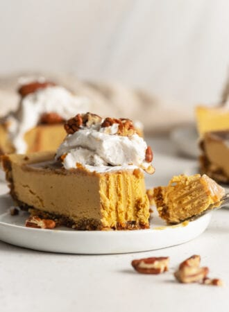 Slice of pumpkin cheesecake topped with whipped cream on a small plate. Bite taken out of slice of cake with a fork.