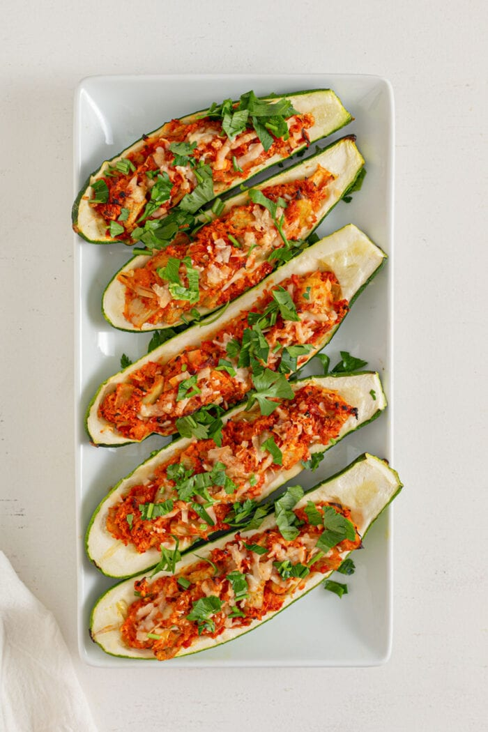 5 stuffed zucchini boats topped with fresh herbs on a rectangular plate.