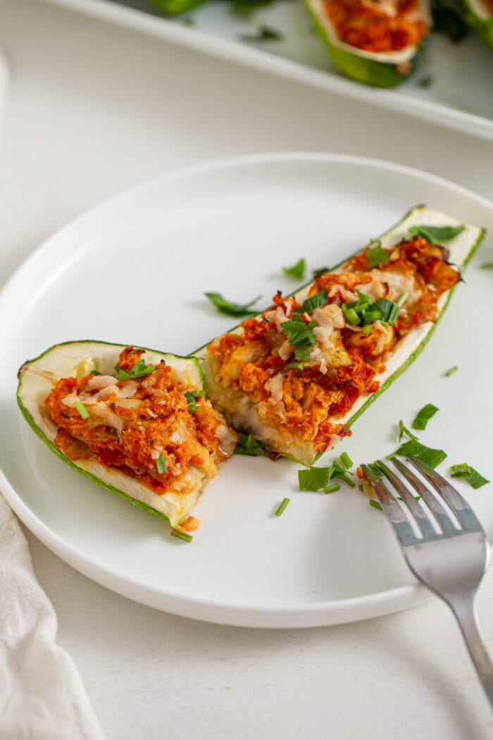 Stuffed zucchini boat cut in half on a plate with a fork.