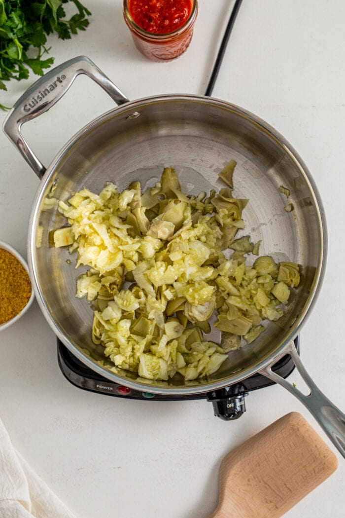 Overhead view of cooked zucchini, artichokes and garlic in a hot skillet.