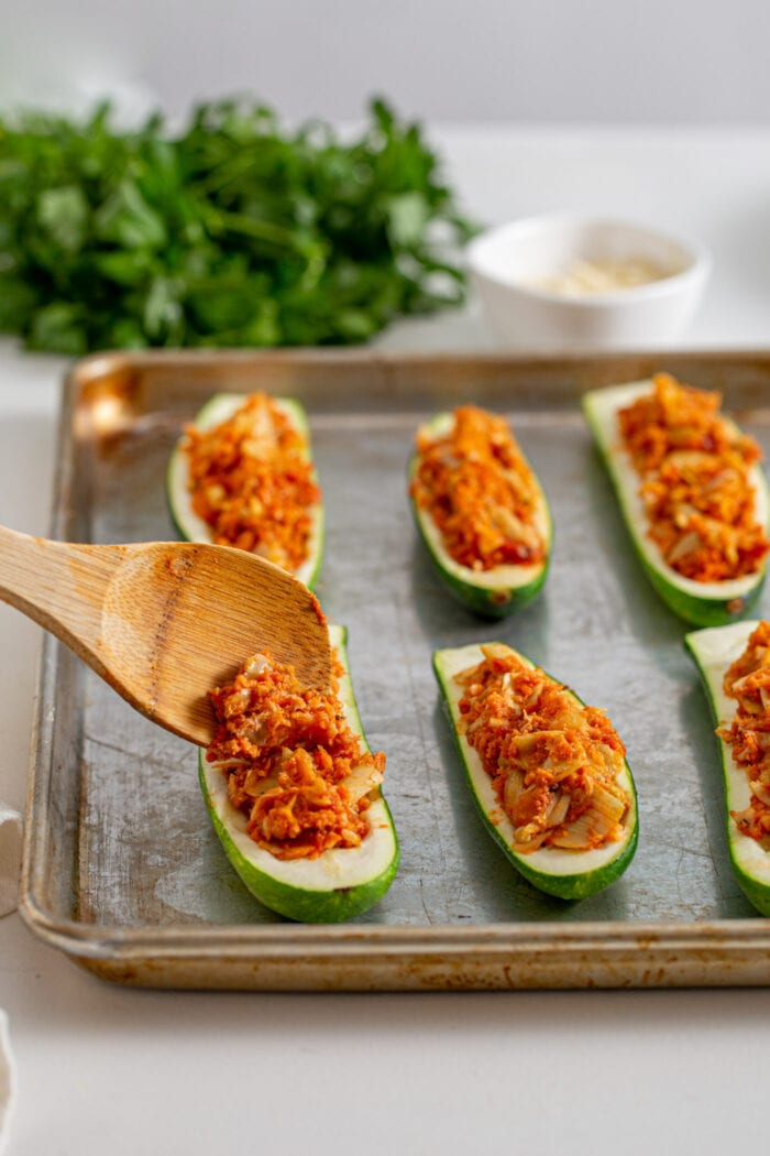 Wooden spoon to add tomato filling to shelled zucchini halves on a baking tray.