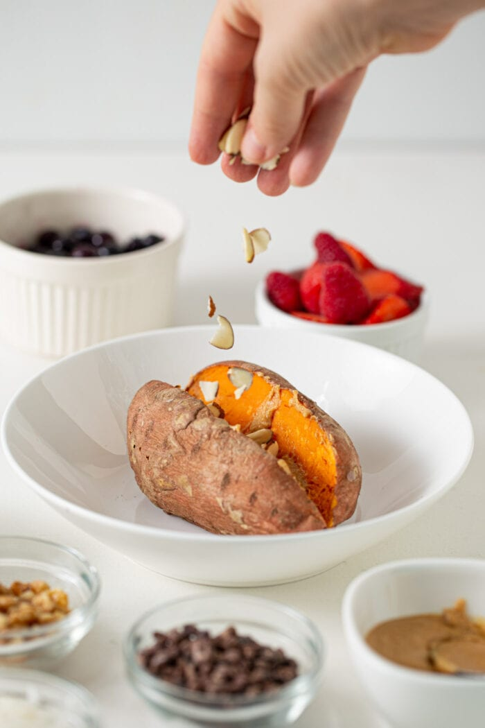 Hand sprinkling slivered almonds over a baked sweet potato in a bowl.