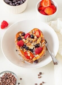 Cut open baked sweet potato in a bowl topped with berries, peanut butter, nuts and coconut.