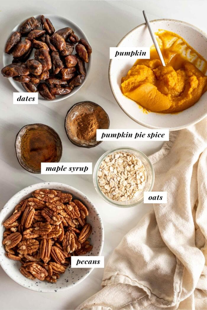 Pecans, dates, pumpkin, pumpkin pie spice and oats in containers. Labelled with text overlay.