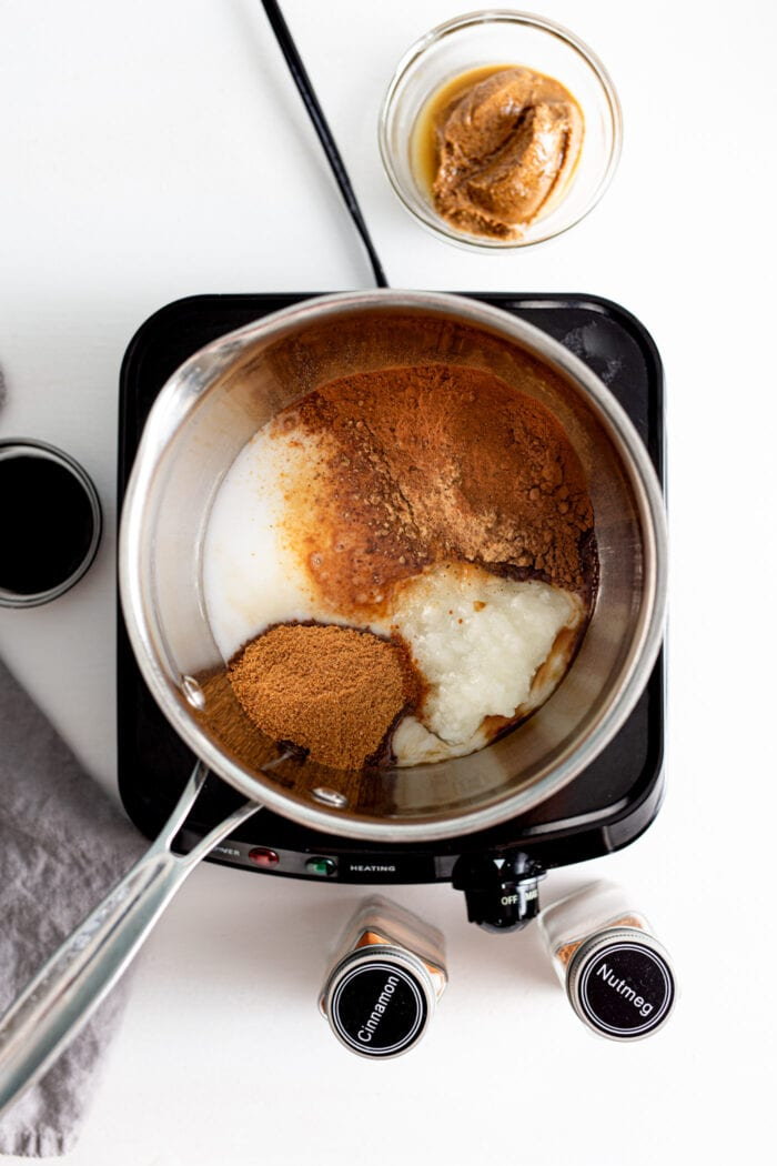 Cocoa powder, sugar and coconut oil in a saucepan on a small cooktop.