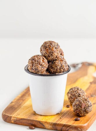 Small cup filled with chocolate energy balls sitting on a cutting board.