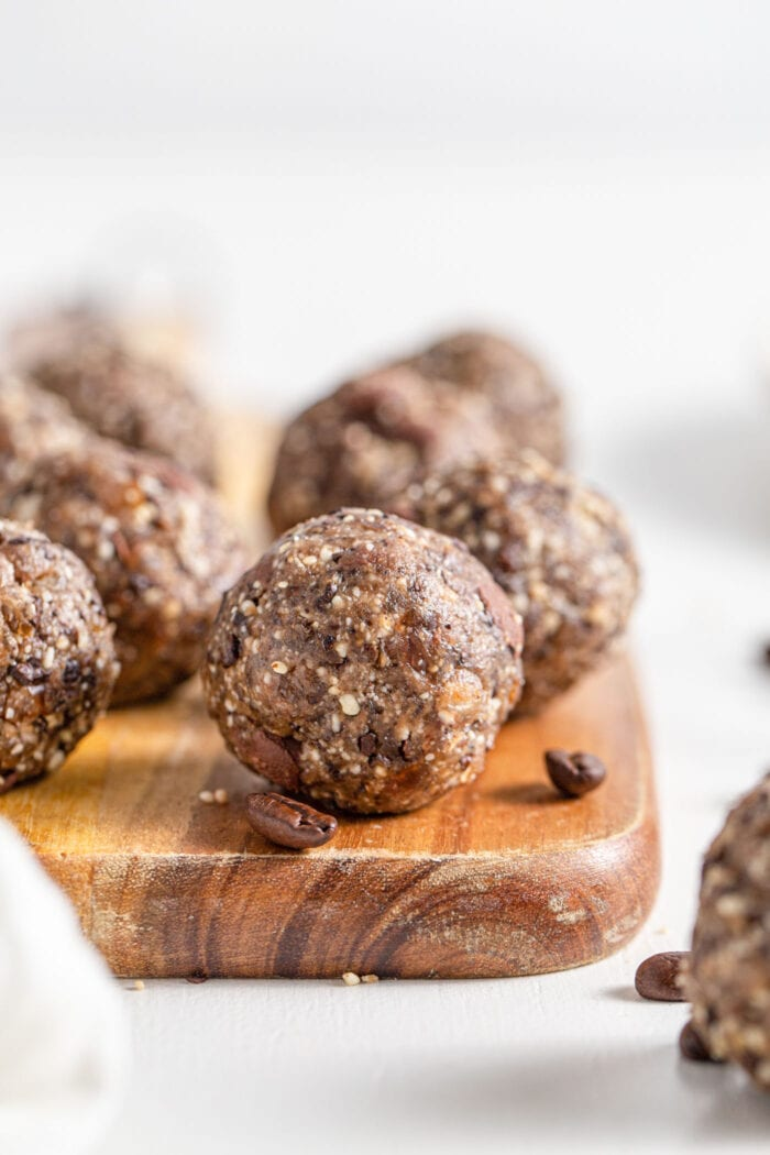 Close up of a chocolate chip energy ball on a cutting board. More balls in background.