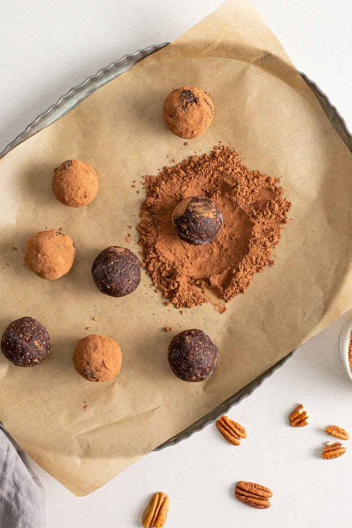 Chocolate energy balls being rolled in cocoa powder on top of parchment paper.