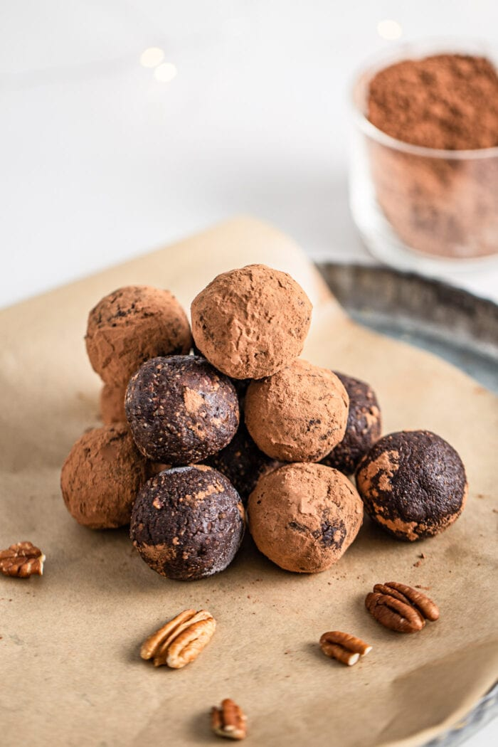 Stack of rum balls on a parchment paper lined plate.
