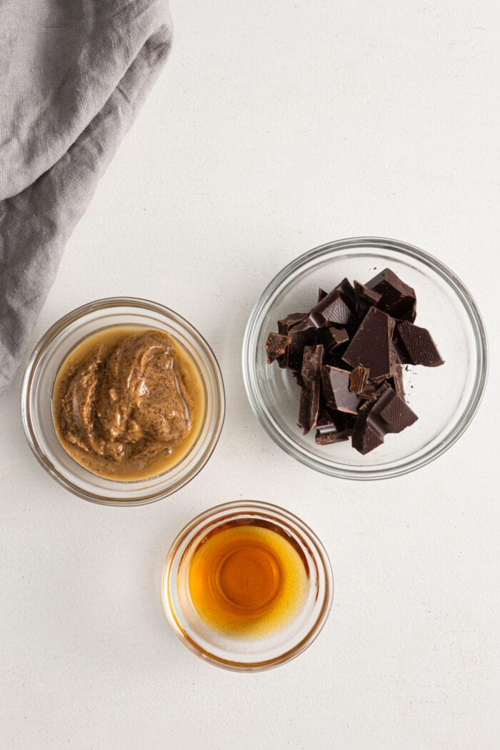 Small dishes of chocolate, maple syrup and almond butter.