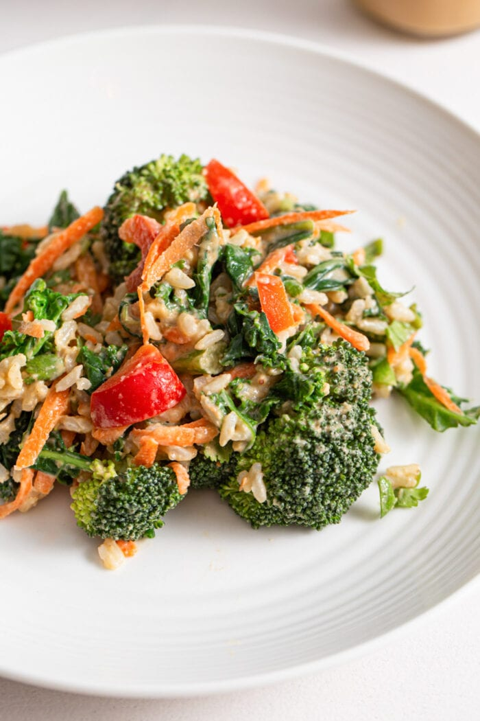 Broccoli, carrot and bell pepper salad with peanut sauce on a plate.