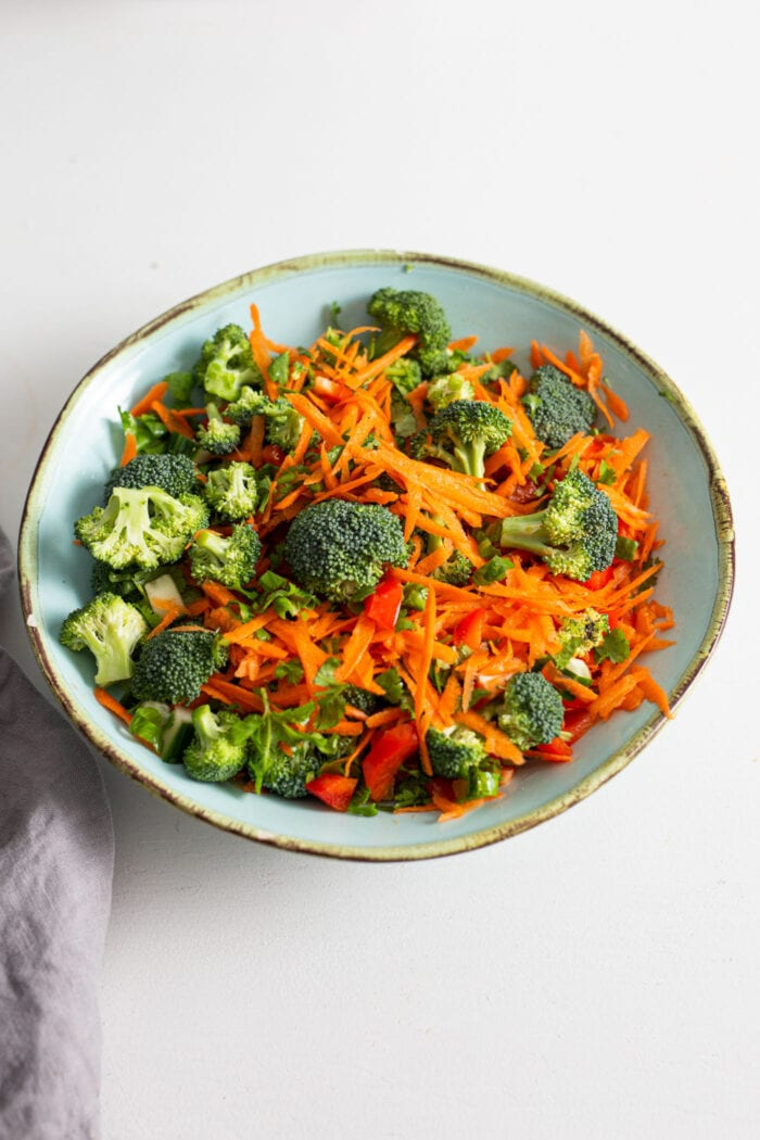 Bell pepper, cucumber, carrot, broccoli and cilantro mixed together in a bowl.