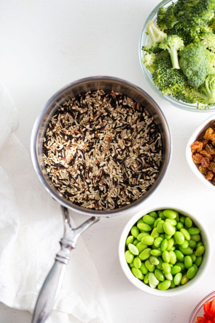 Cooked wild rice in a pot with bowl of edamame and broccoli beside it.