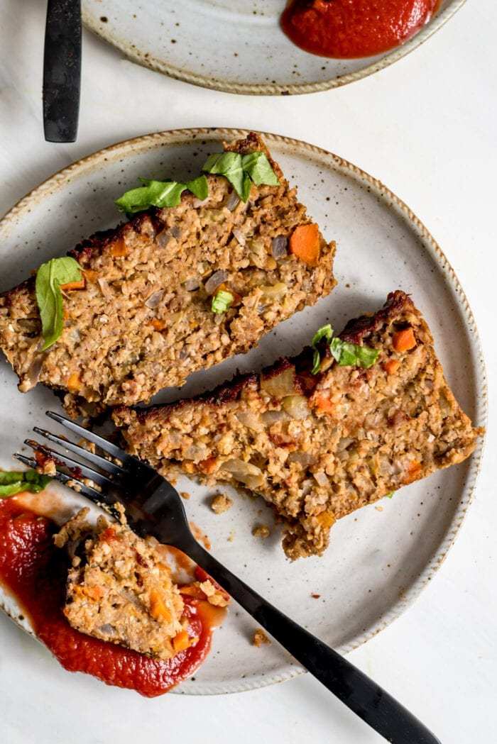 Two slices of vegan chickpea meatloaf on small plate with ketchup. Fork rests on plate.