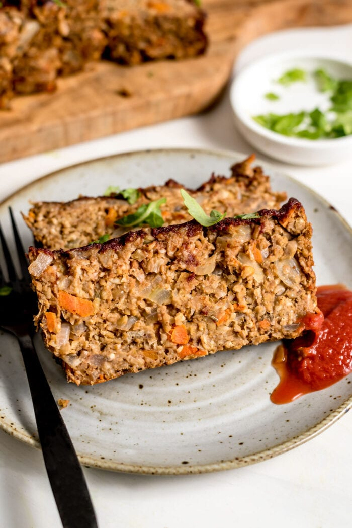 Two slices of vegetarian chickpea meatloaf on a plate with ketchup. Fork rests on plate.