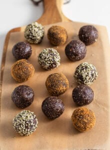 Chocolate energy balls rolled in coconut sugar and hemp seeds on a cutting board lined with parchment paper.