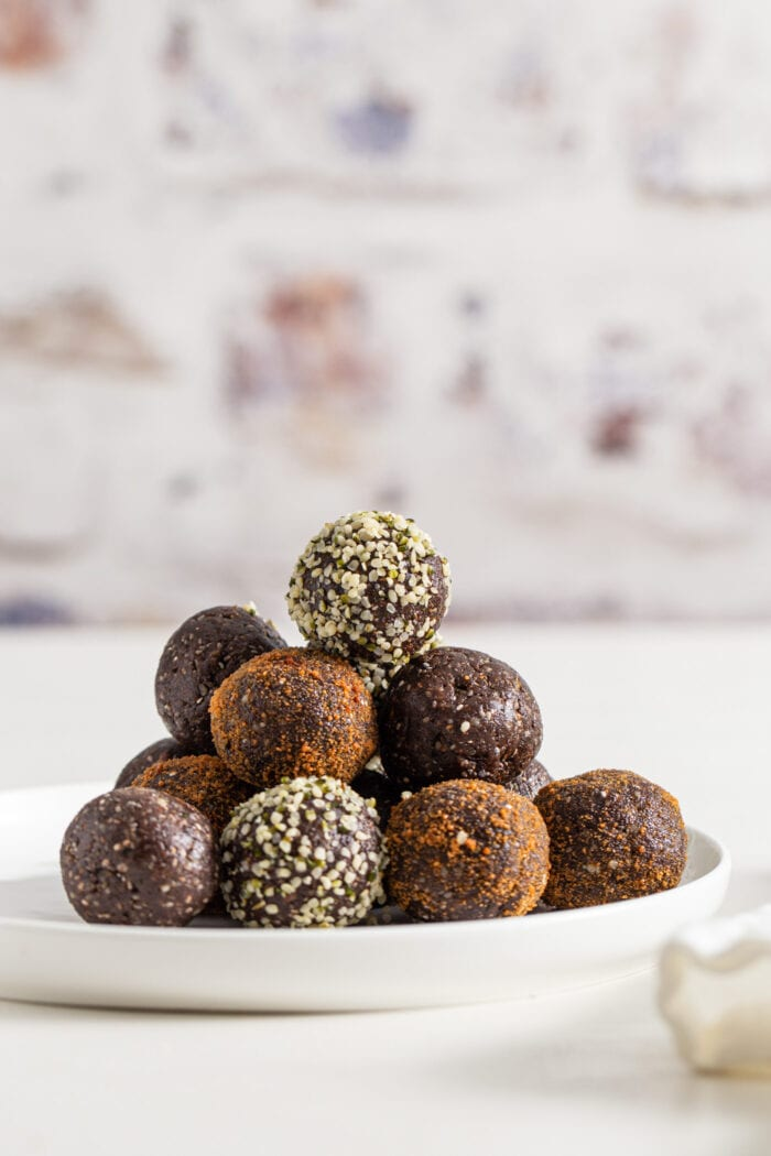 Stack of chocolate covered energy balls on plate against a brick background.