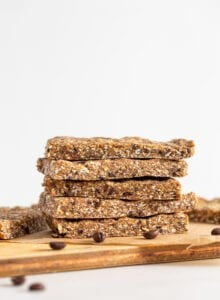 Stack of 4 energy bars on a cutting board. Coffee beans scattered around.