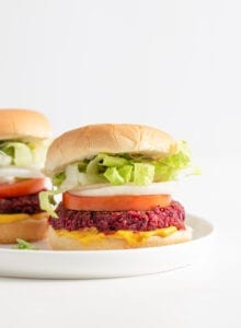 Two beet burgers on buns with onion, lettuce and tomato.