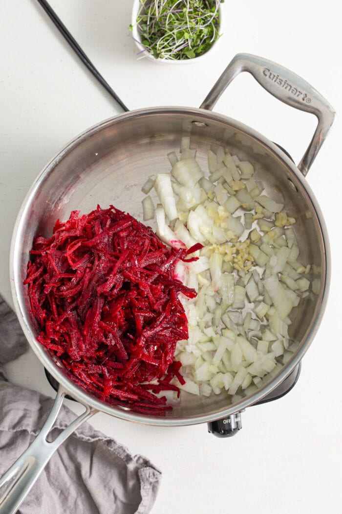 Grated beet, onion and garlic cooking in a skillet.