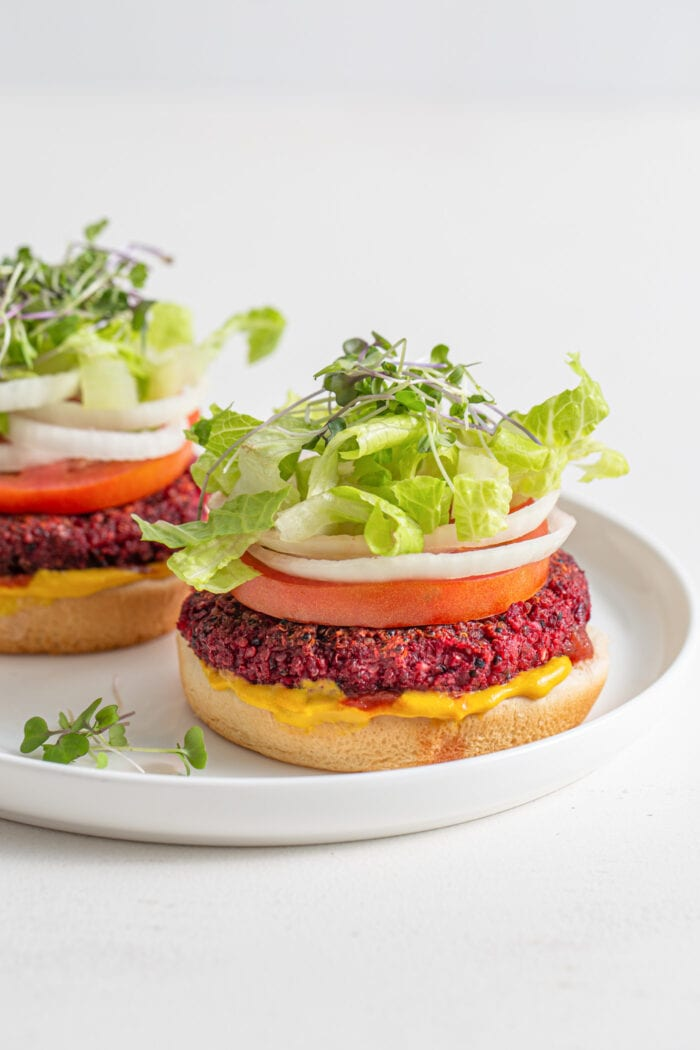 Two beet burgers on buns with lettuce, sprouts, tomato, onion, mustard and ketcup.