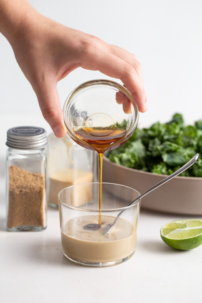 Pouring a dish of maple syrup into a glass of tahini with a spoon it.