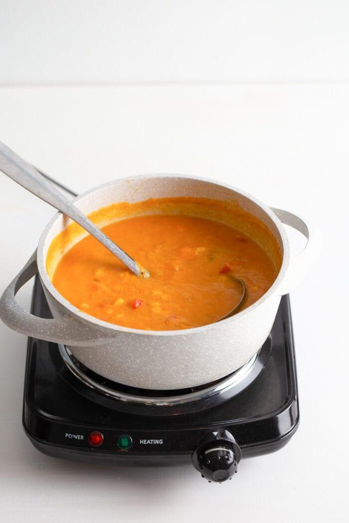 Cream sweet potato corn chowder in a soup pot. Spoon rests in pot.