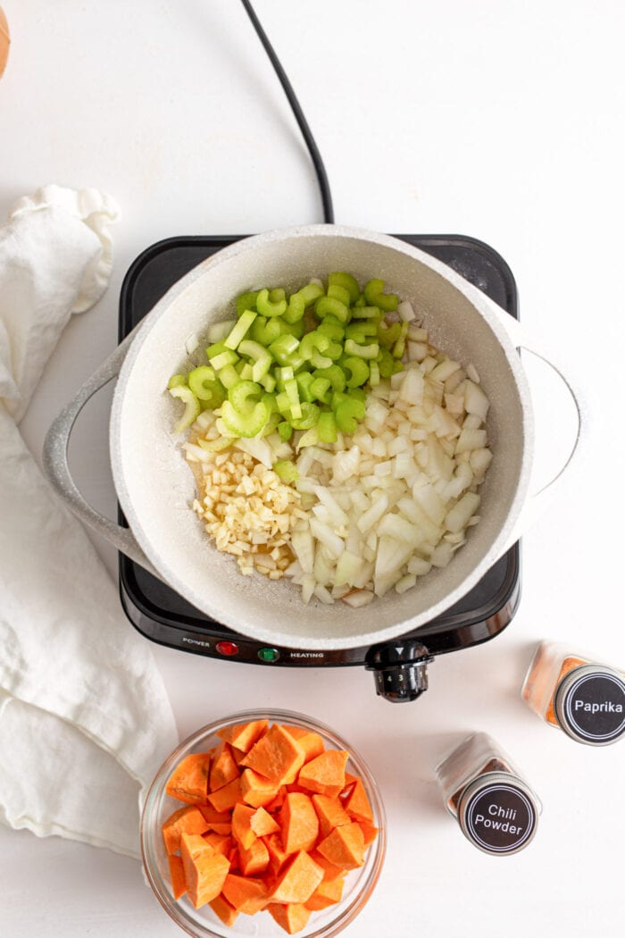 Onions, garlic, ginger and celery in a pot cooking on a small cooktop.