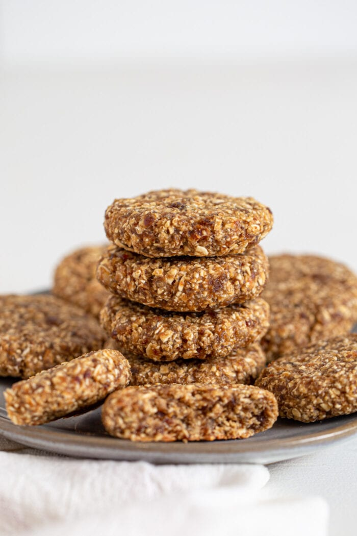 4 oat date cookies stacked on a plate. More cookies sit around the stack.