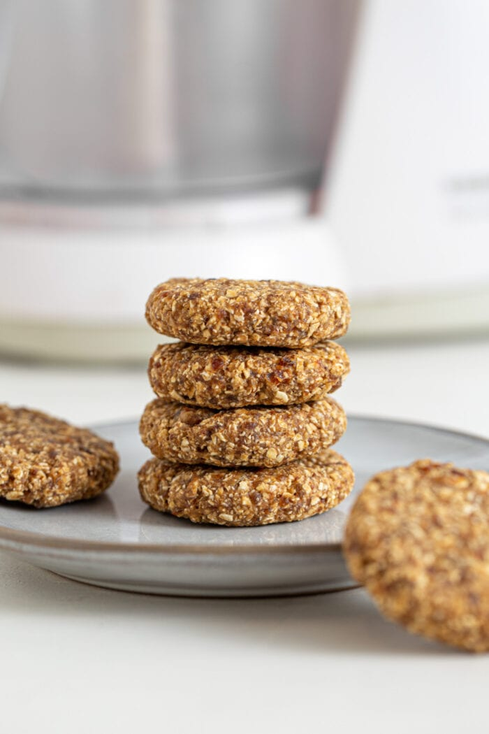 Stack of 4 tahini oat cookies on a plate. 2 cookies rest beside the stack on the plate.