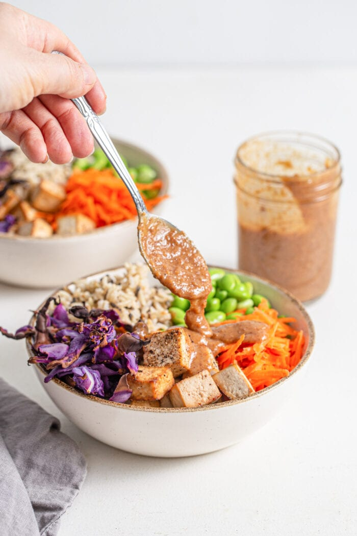 Hand spooning sauce over a colourful bowl of rice, tofu and vegetables.