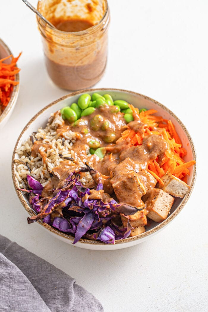 Bowl of cabbage, rice, tofu, carrot, edamame. Topped with creamy peanut sauce.
