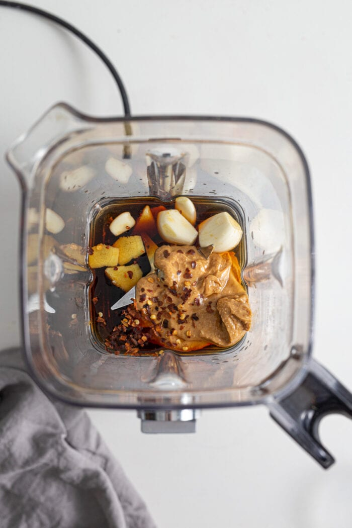 Peanut butter, garlic, soy sauce and ginger in a blender container.
