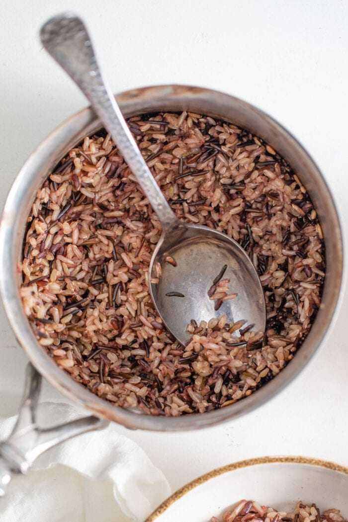 Wild rice cooking in a pot. Spoon rests in pot.