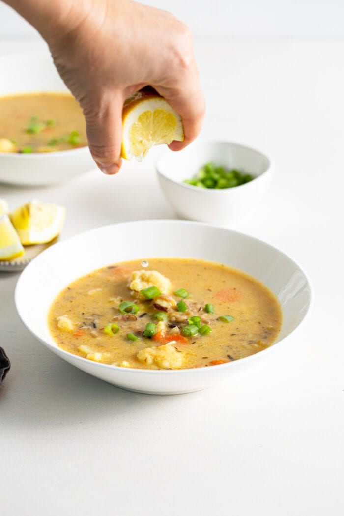 Hand squeezing lemon into a bowl of cauliflower and carrot soup.