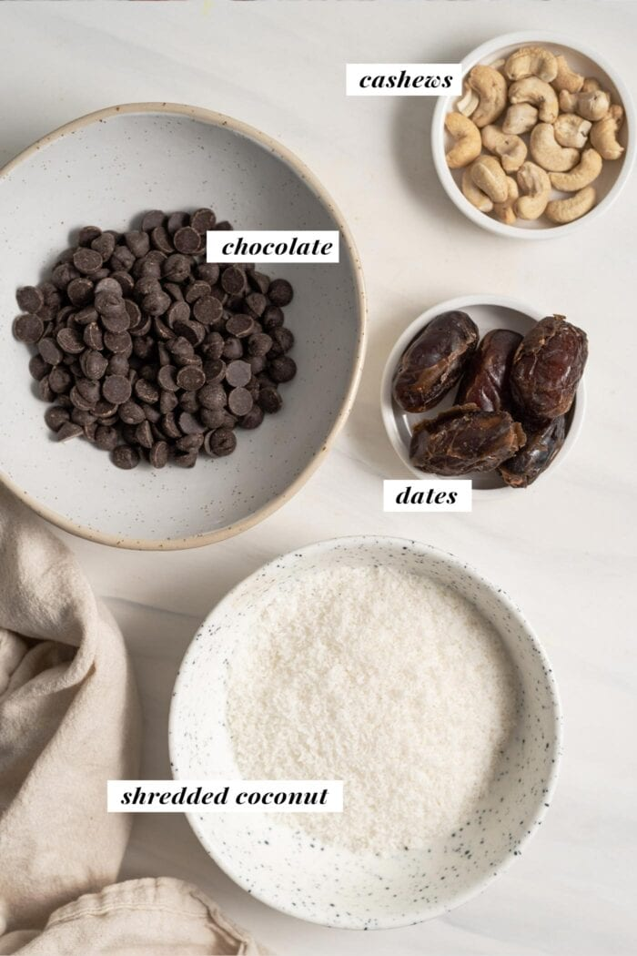Coconut, cashews, dates and chocolates in bowls, labelled with Coconut, cashews, dates and chocolates in bowls, labelled with text overlay. overlay.