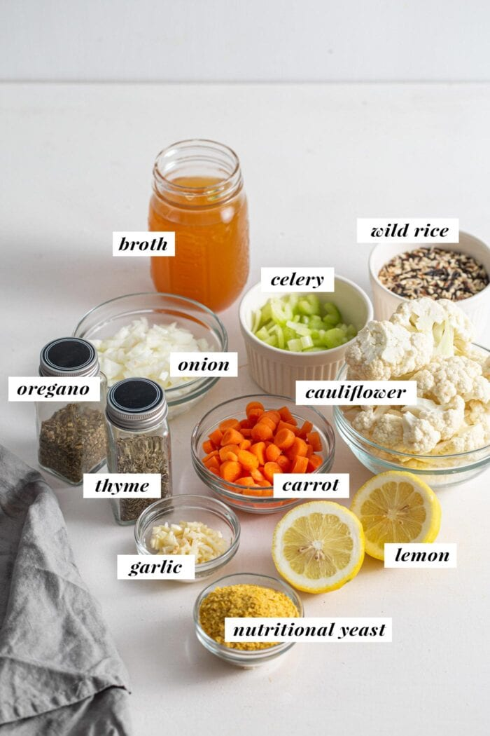 Visual of all ingredients needed for making a cauliflower wild rice soup. Ingredients are labelled with text overlay.