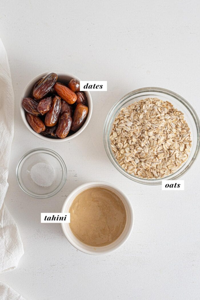 Oats, dates and tahini in bowls. Text overlay labels each ingredient.