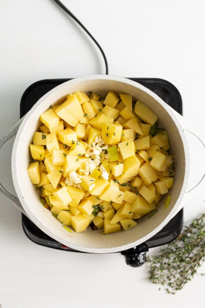 Diced potatoes cooking in a soup pot on a small stovetop.