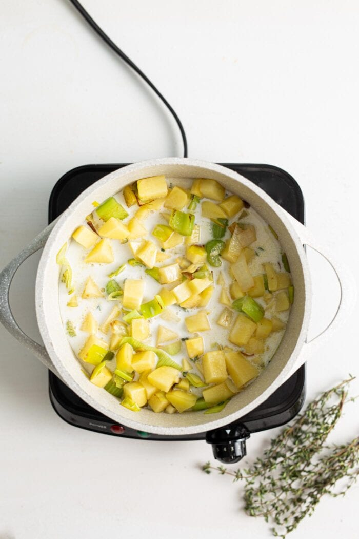 Peeled and diced potatoes cooking in a coconut milk broth in a pot on a small cooktop.