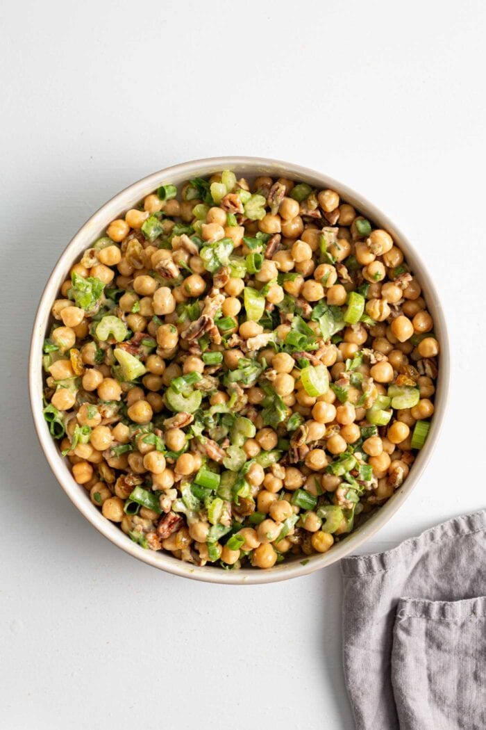 Mixed up curried chickpea salad in a large salad bowl.